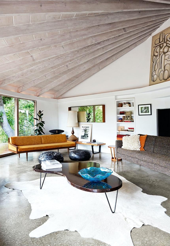 Stue med stort hvidt skind liggende på gulvet med sofaer omkring