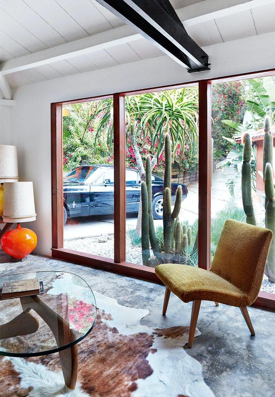 Vintage stol stående foran vindue med brunt og hvidt koskind liggende på gulvet
