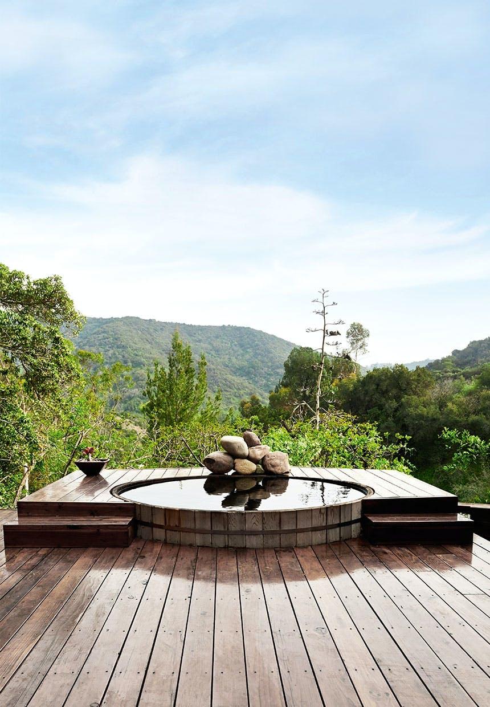 Udendørs boblebad bygget ned i træterrassen med skøn udsigt over natur