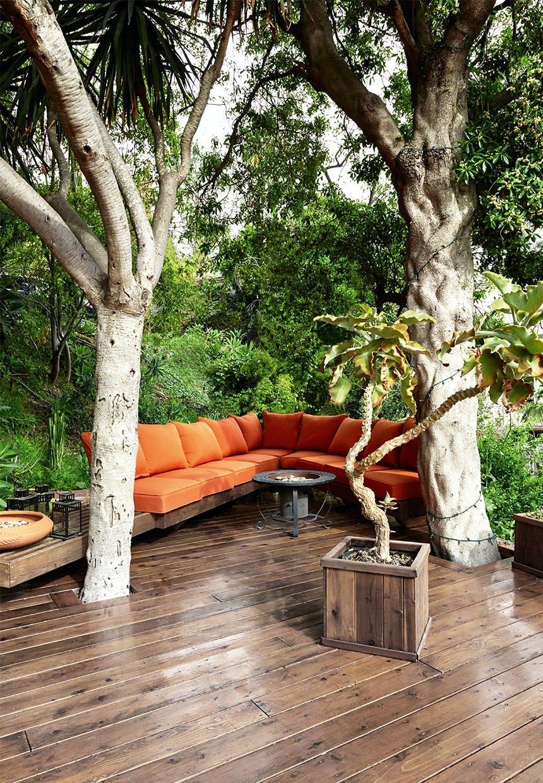 Lounge-område på træterrassen med specialbygget sofa med orange hynder og puder