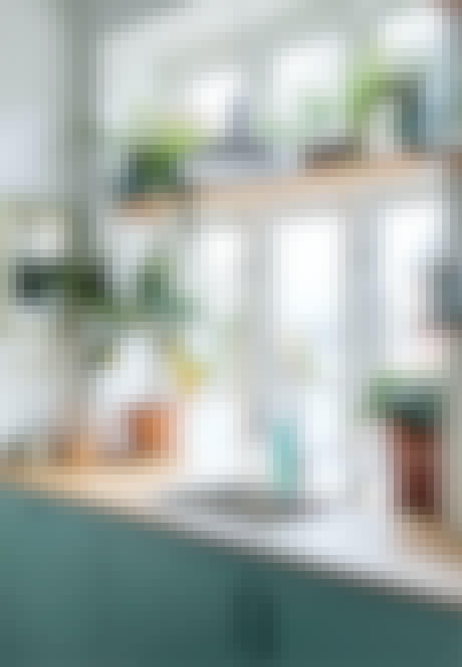 Stålhåndvask i køkkenbordet foran vinduet med hylder omkring og diverse planter