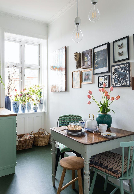 Spisekrog i køkkenet med et lille ældre spisebord og genbrugsstole