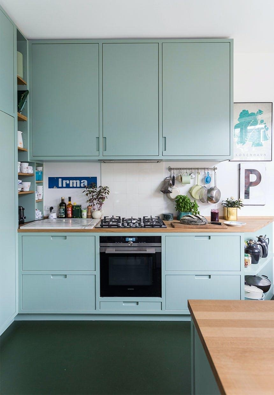 Køkken med skabe og hylder i mintgrøn, ovn og gaskomfur, og en marmorbordplade