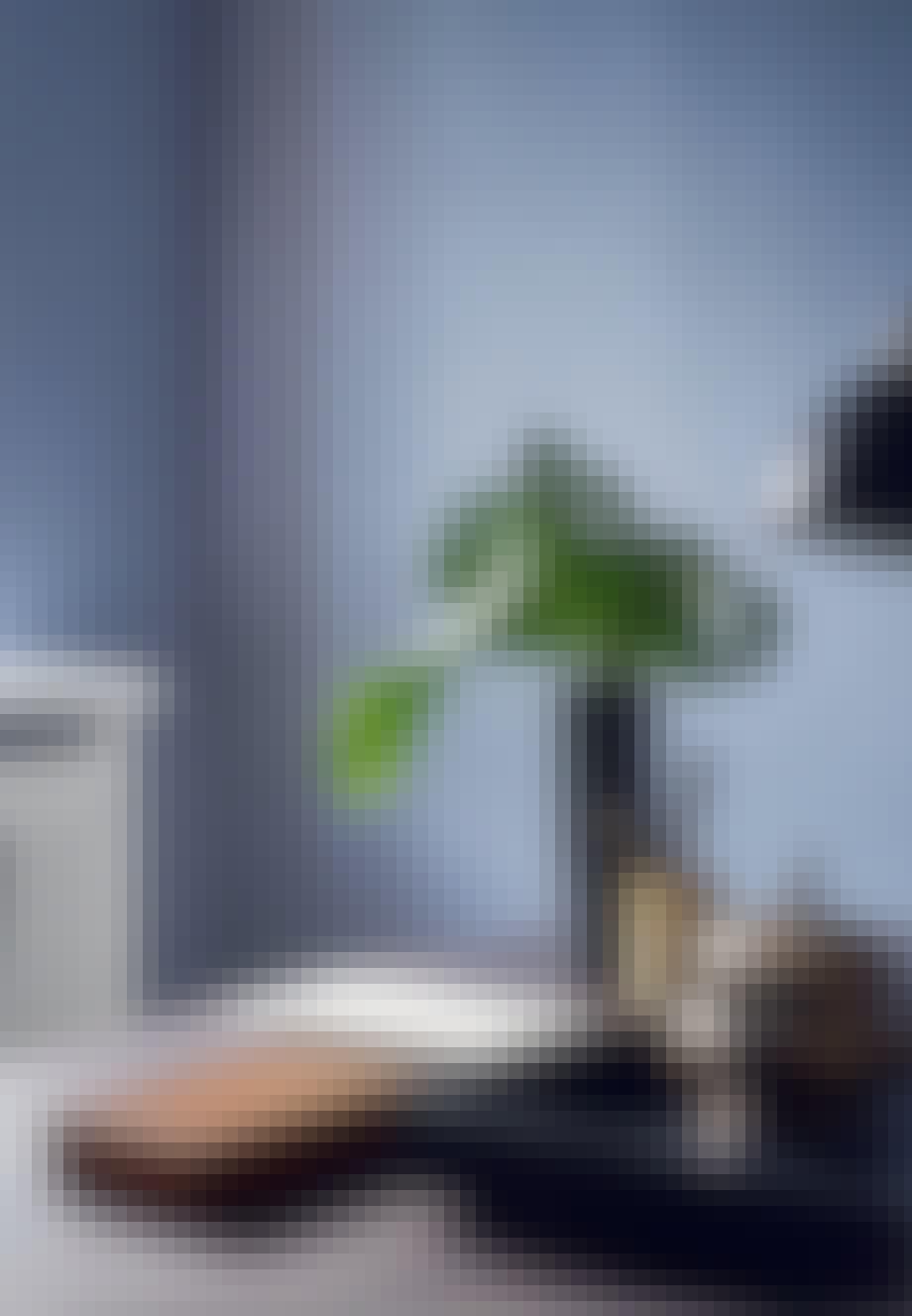 Sort marmorvase, læderbakke, røgelseskar og bordlampe på skrivebordet