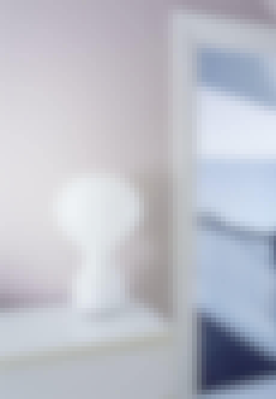 Skulpturel hvid lampe stående på hylde i soveværelset