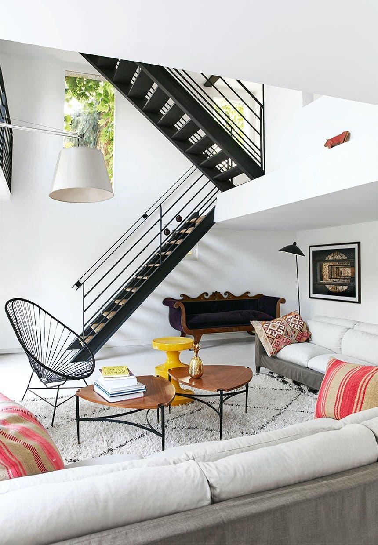 Stue med store flydere af sofaer og en antik velourbetrukket sofa i hjørnet under den rustikke trappe