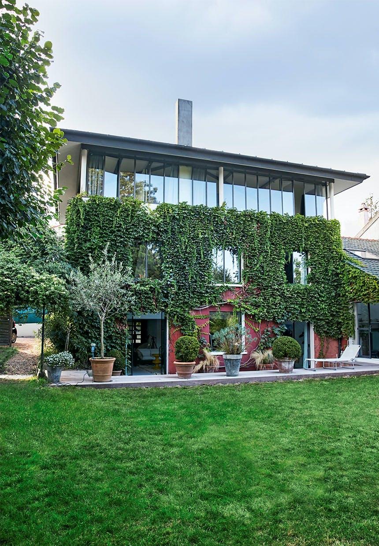 Facade af bagsiden af huset med terrasse, have, vedbend på facaden og øverste etage kun af glasvægge