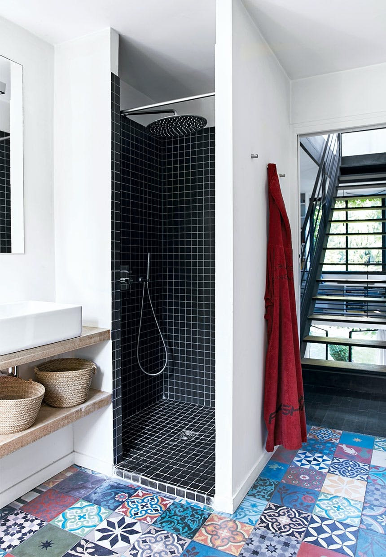 Badeværelse i vovet stil med farverige fliser med mønstre på gulvet og sorte mosaikfliser i brusekabinen