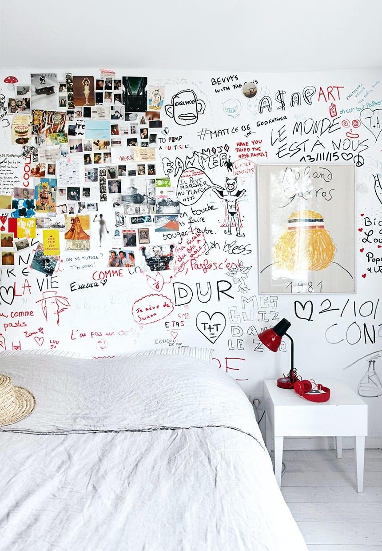 Teenageværelse holdt i hvidt men en graffitivæg med venners underskrifter, tegninger og sjove ord