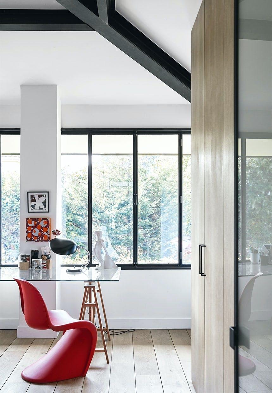 Gæsteværelse med store vinduer, stort garderobeskab og et skrivebord med glasplade og Verner Panton stol