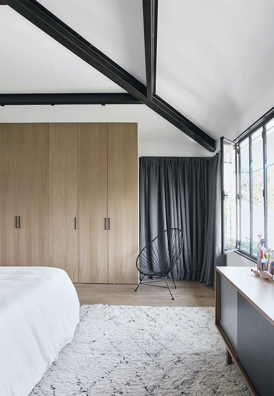 Soveværelse hvor endevæg er garderobeskabe i egetræ, med gulvtæppe fra Marokko og skænk fra 50'erne