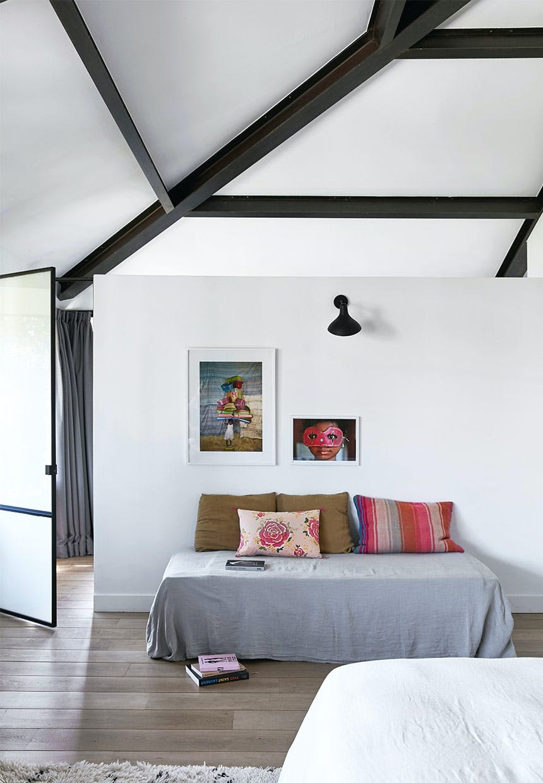 Daybed i soveværelsets ene ende med farverige puder og billeder på væggen