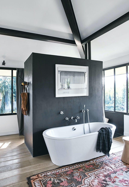Stort badeværelse med hvidt badekar og en sort boks der gemmer brusekabinen