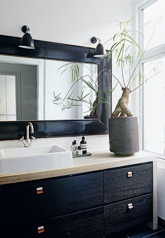 Badeværelsesmøbel med sorte skuffer og hvid håndvask med stort spejl med sort ramme hængende over
