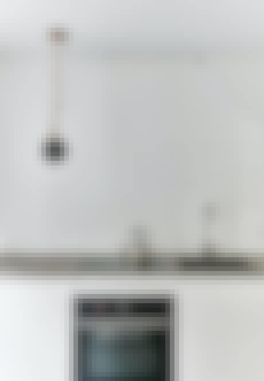 Enkel, skulpturel lampe af Søren Rose hængende over køkkenbordet