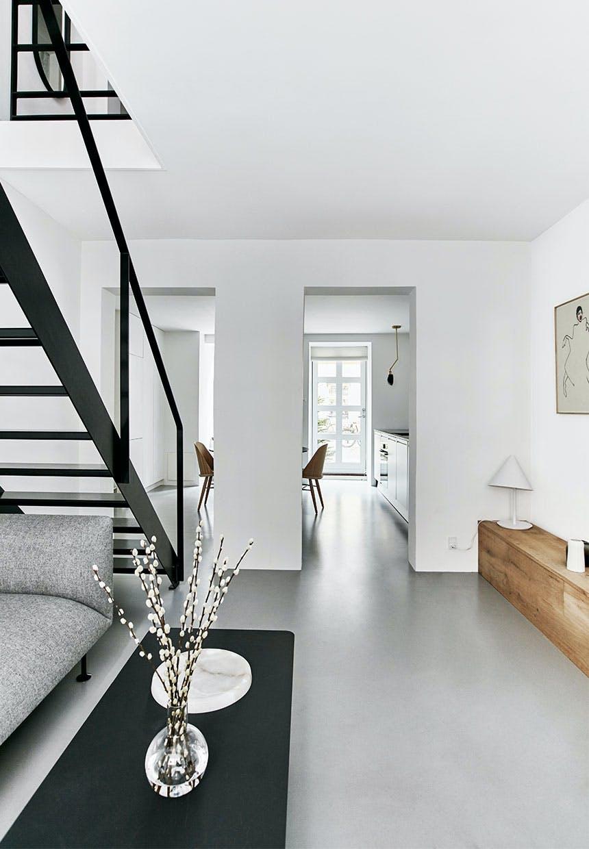 Kig fra stue til køkken hvor lysegråt epoxy-gulv går helt igennem