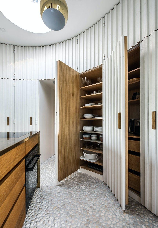 Skjulte indbyggede buede skabe i køkkenet gemmer på service og maskiner