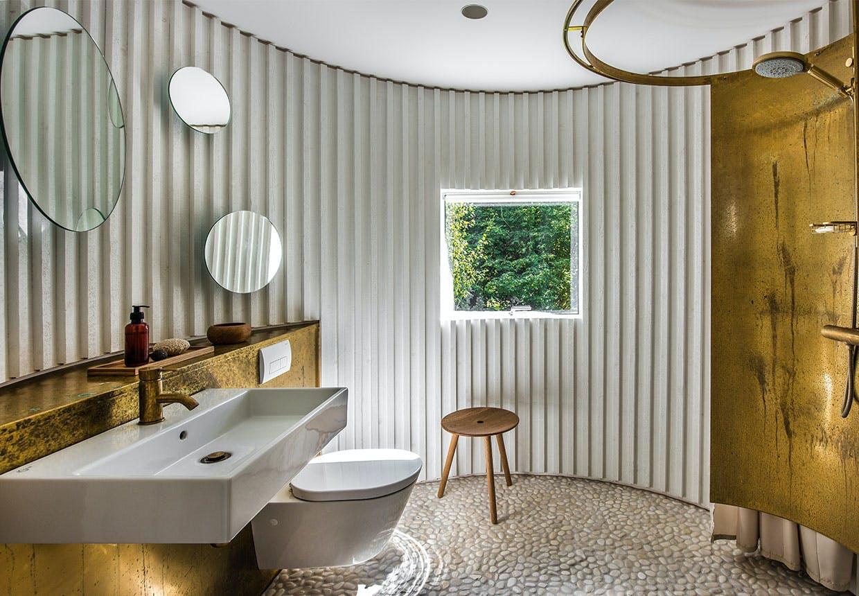 Badeværelse med bruseplads med en dekorativ og funktionel messingplade