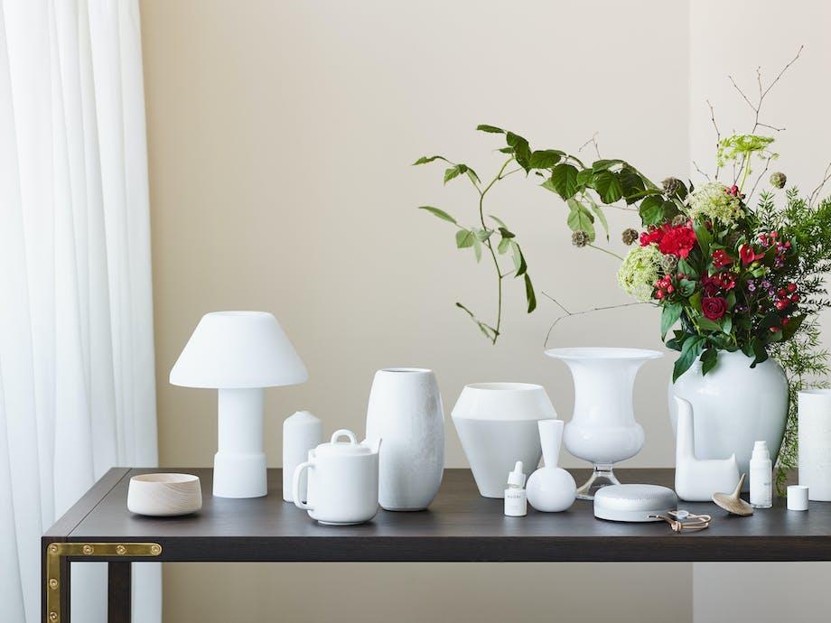 Bord med med hvide genstande i glas, porcelæn og stentøj.