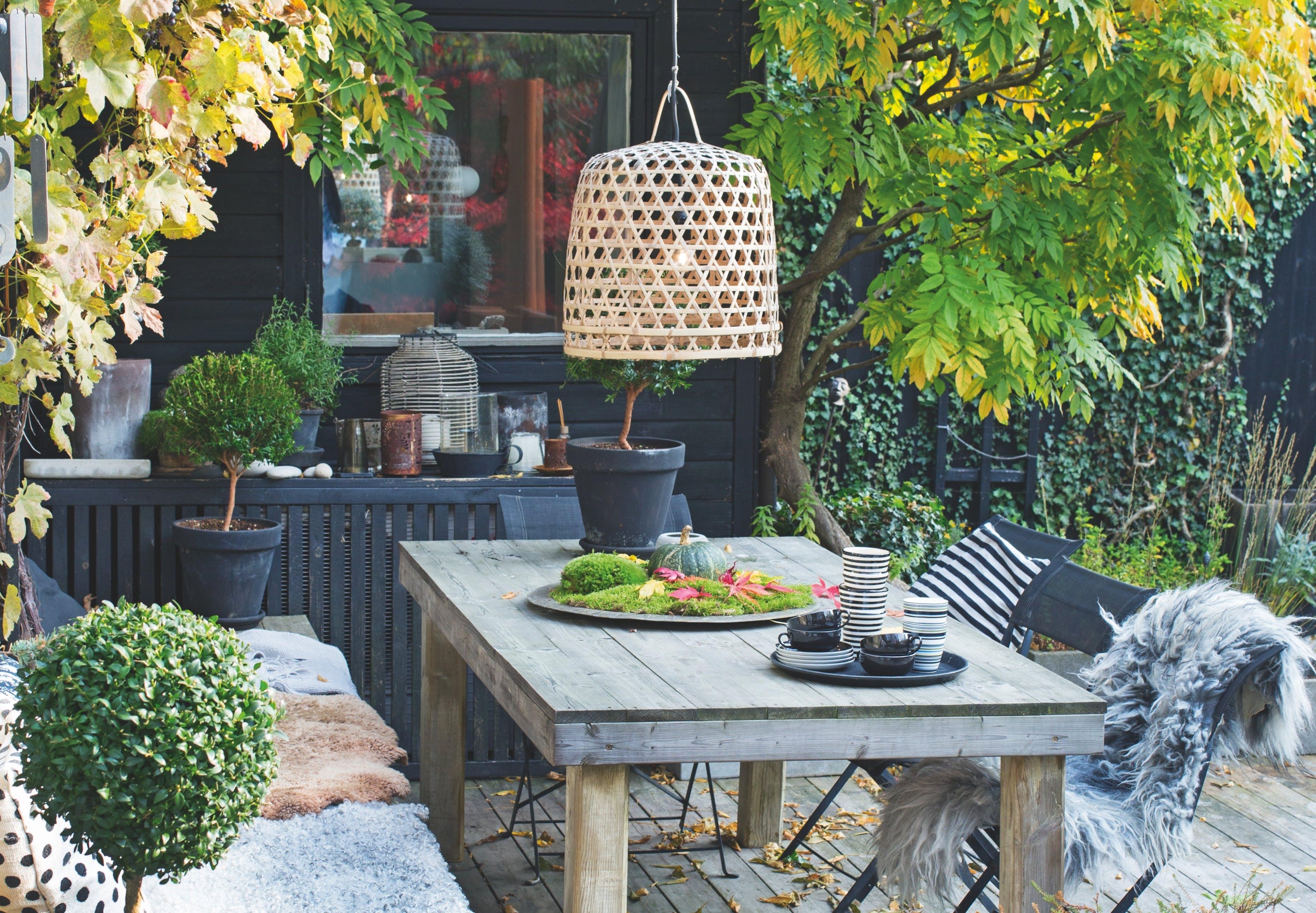 efterårshave med terrasse med bord og plaider og stole