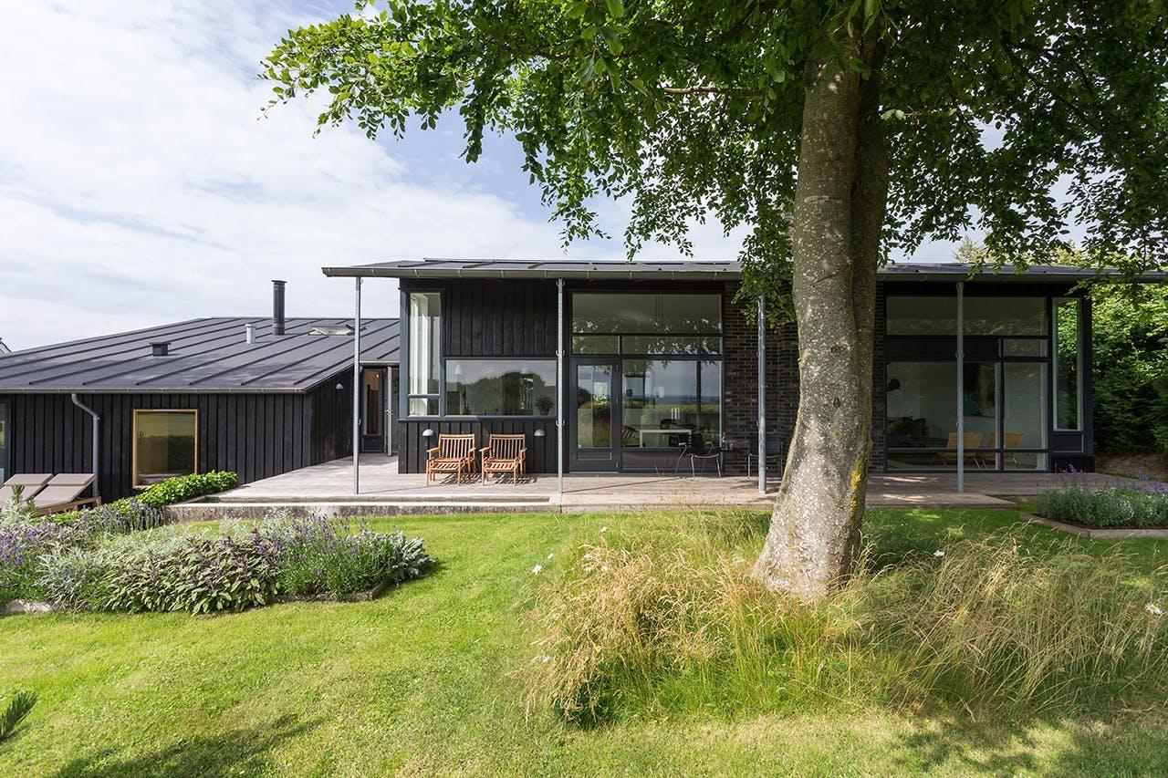 hus i træ malet sort i grønne omgivelser