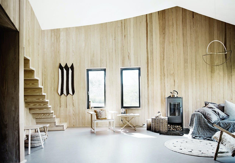 Stue med vægge af træ, simpel indretning, skulpturel trappe og brændeovn