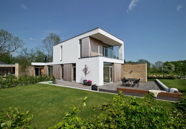 Facade af miks af tegl, cedertræ og hvidt facadepuds på begge etager