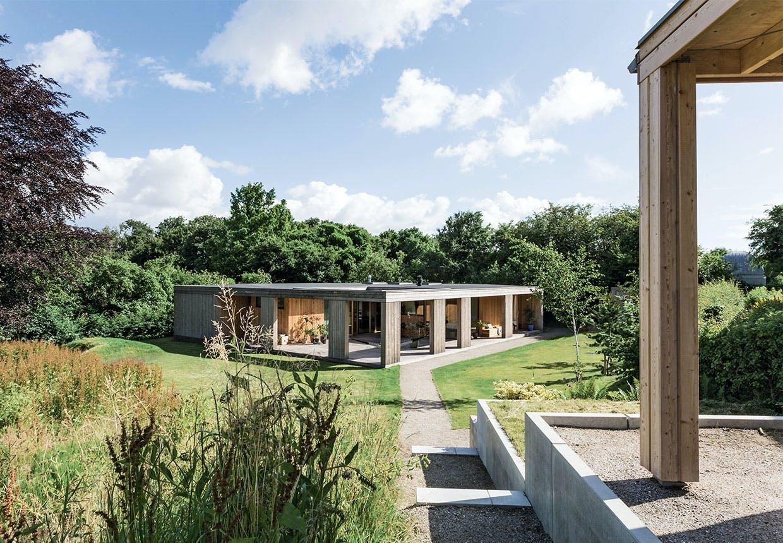 Udsigt over det kubeformede hus med have og lille skov til