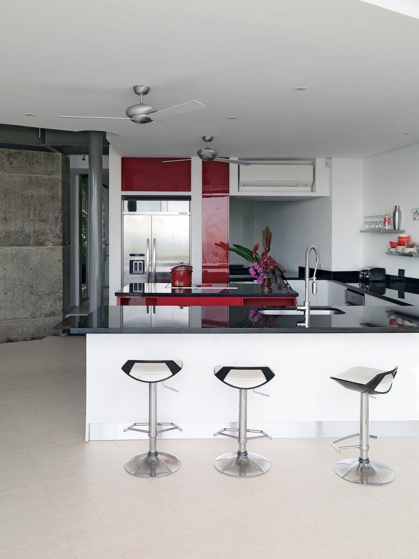 Køkken i højglans med røde detaljer og køkkenø
