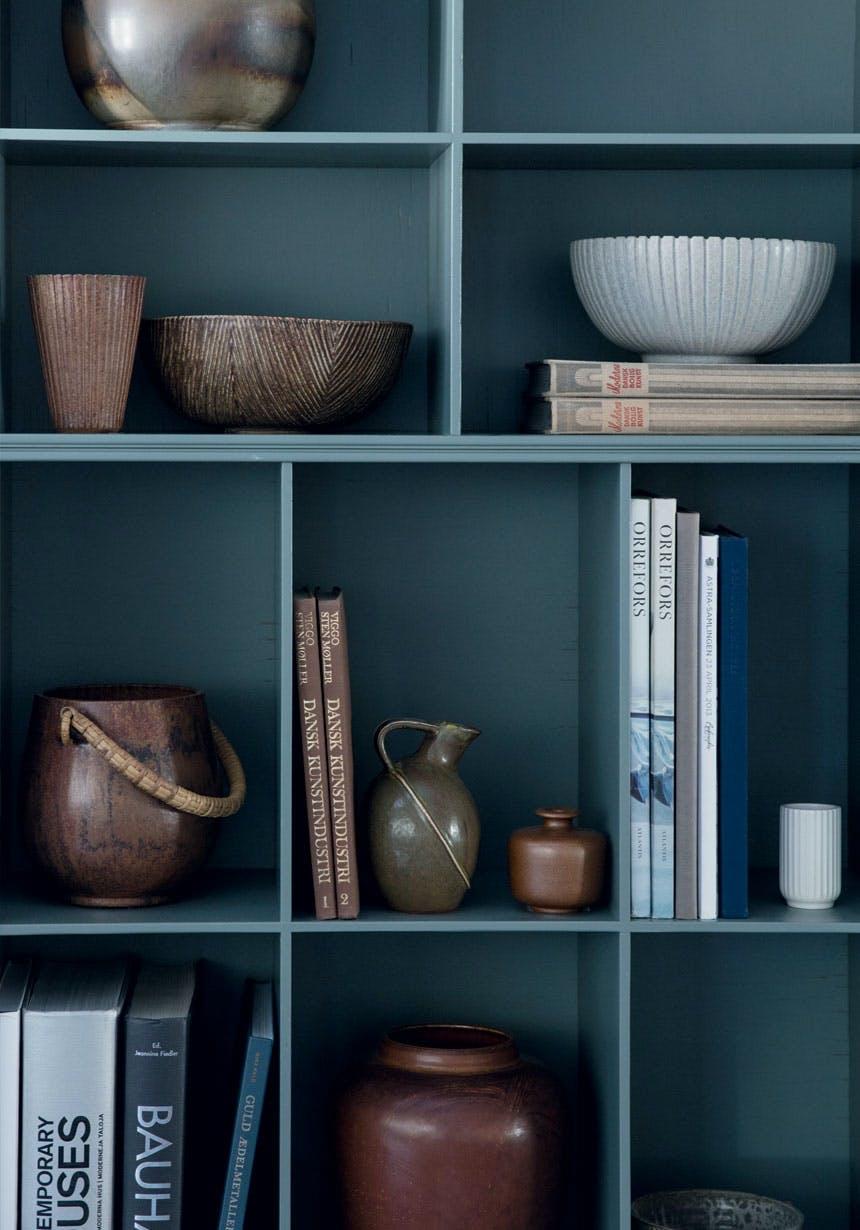Reol med keramik og bøger i brunlige nuancer