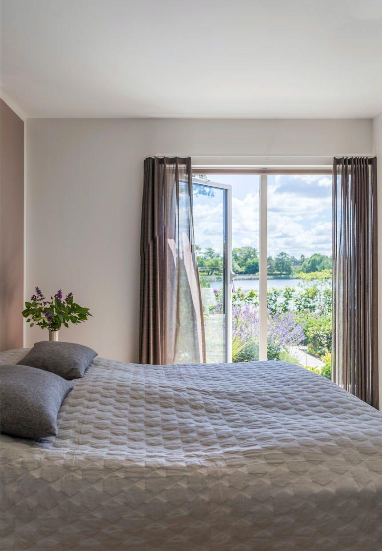 Soveværelse i rolige nuancer og mørke gardiner