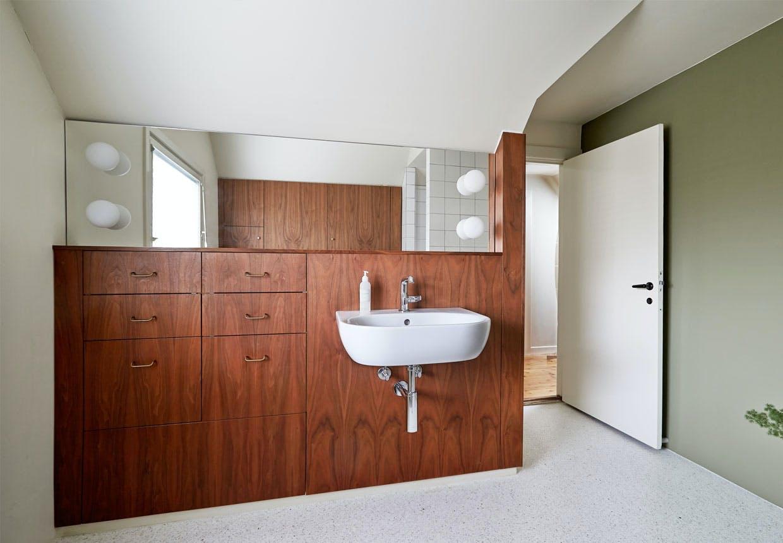 Stort badeværelse med møbler af valnød
