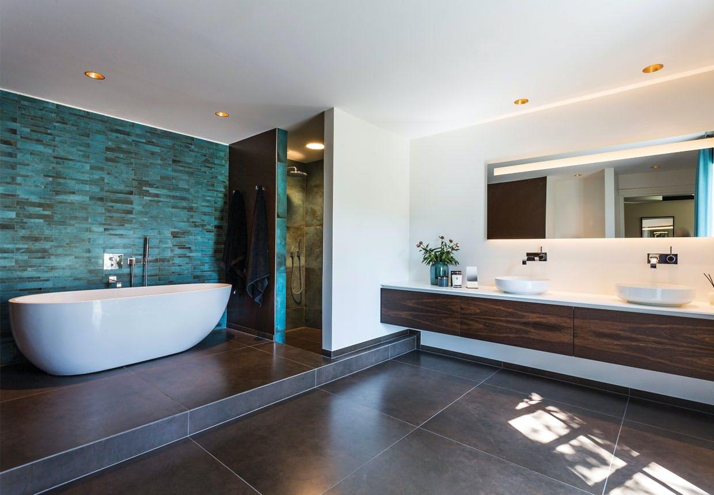 Personlig hotelbad med badekar og grønne fliser i nyopført bandegård