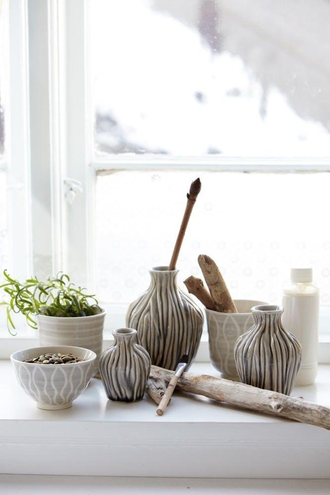 En vindueskarm fuld af fine skåle og vaser