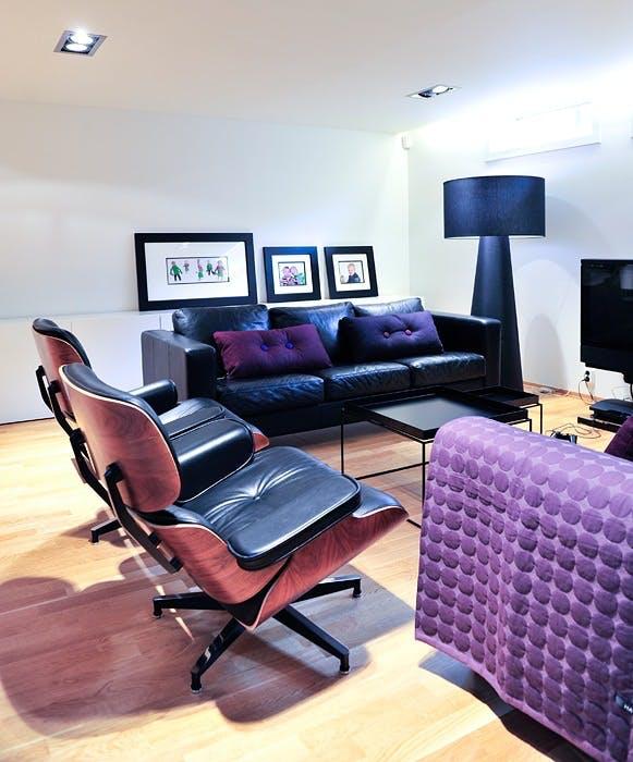 To skinnsofaer fra Ikea får selskap av to Eames loungestoler rundt bordene fra Hay. De lilla putene og teppet er også fra Hay.
