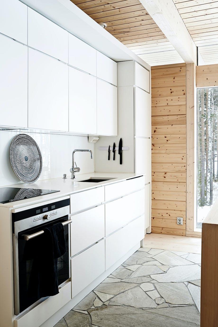 Hvitt kjøkken og grått steingulv.