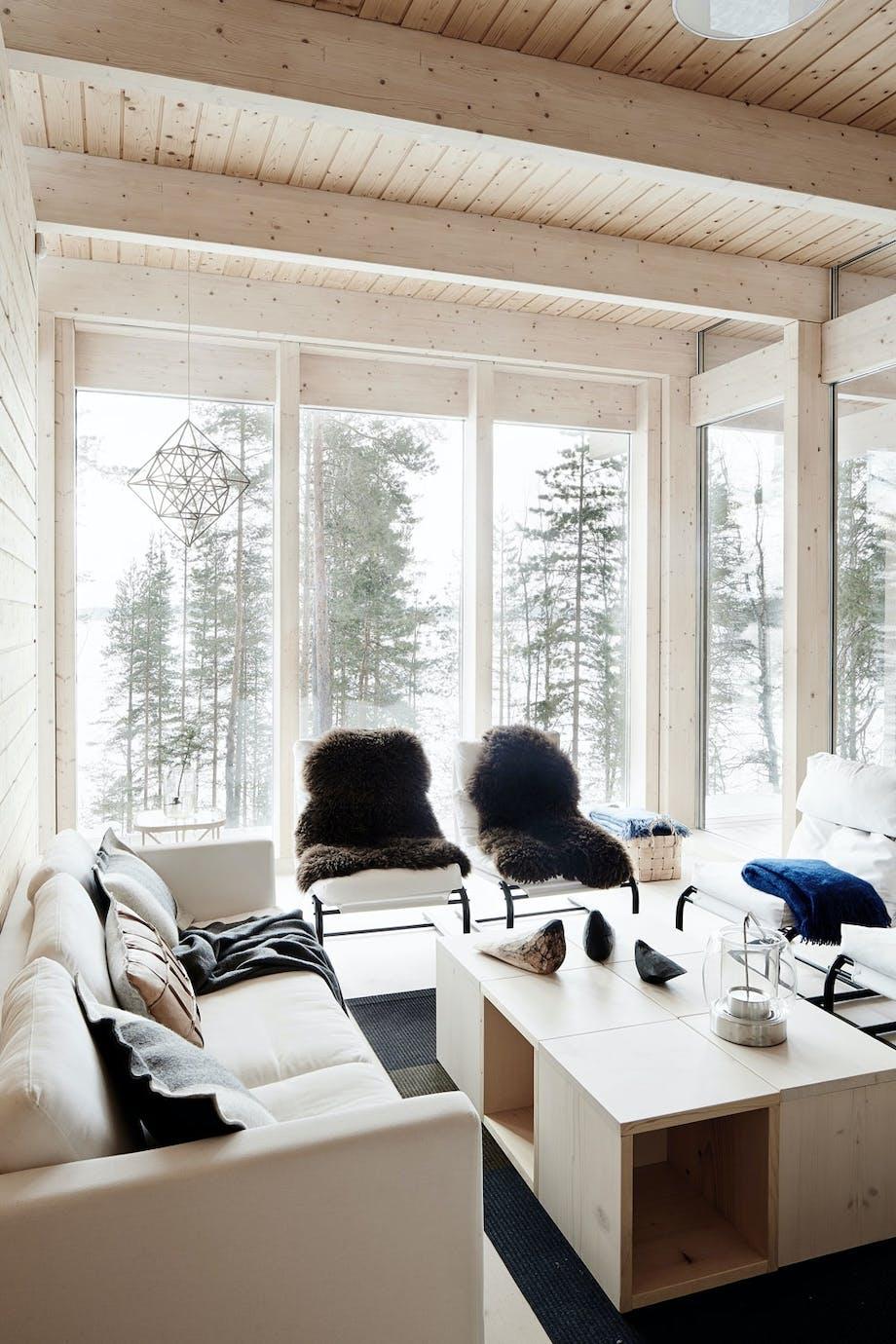 Lyst treverk og store vinduer i stuen.