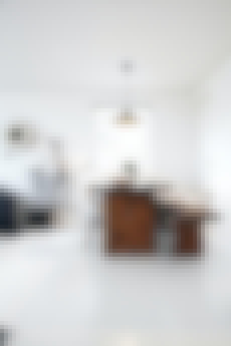 Hvitt kjøkken med robuste eikemøbler og Tom Dixon-lampe
