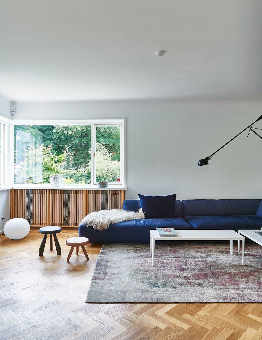 Stue med fiskebensparkett og mørkeblå sofa i funkisvilla