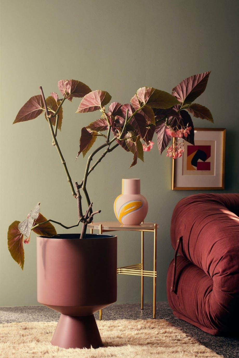 Interiørmiljø i burgunder og grønt, med vase fra designsamarbeidet mellom Stine Goya og Kähler