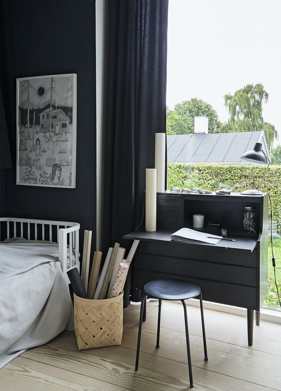 Sort skrivepult, mørkeblå bordlampe, plakat fra Ikea