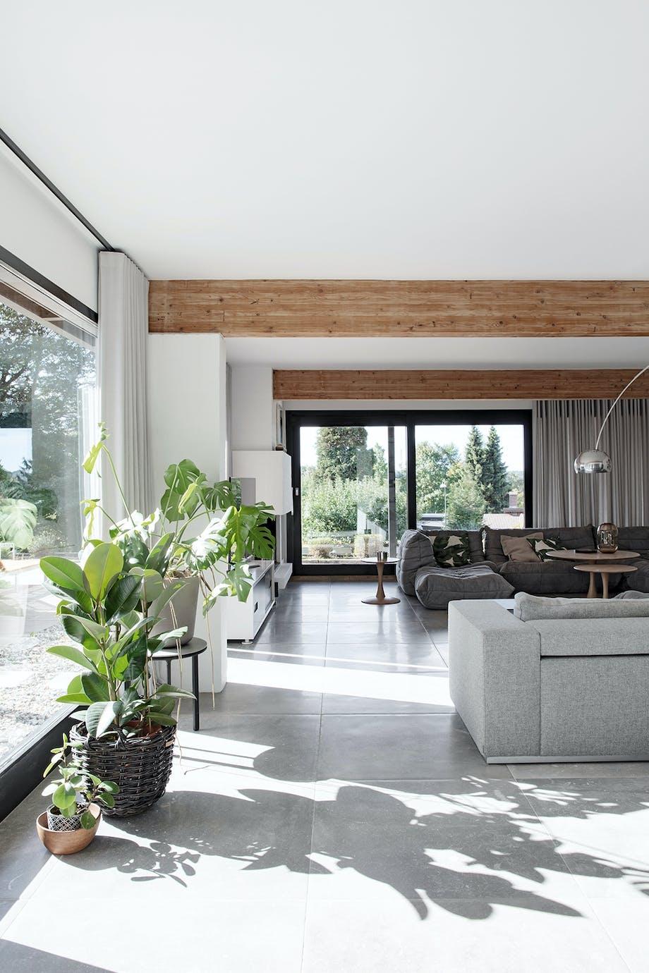 Stue åben pejs grønne planter store vindespartier grå keramiske klinker