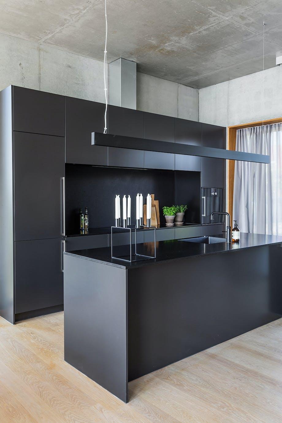 Sort Køkken Multiform betonvægge egetræsgulv