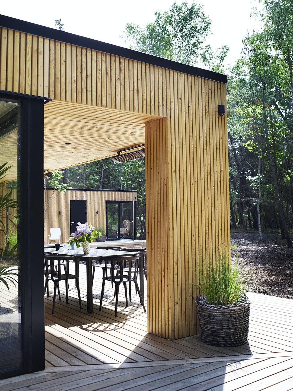 Husets terrasse i træ med spisebord og stole.
