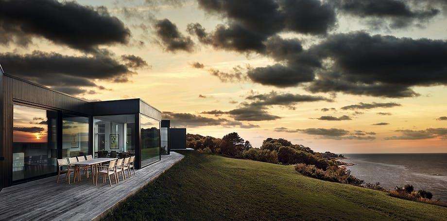 Hus på bakke med ugsigt overvandet ved solnedgangen