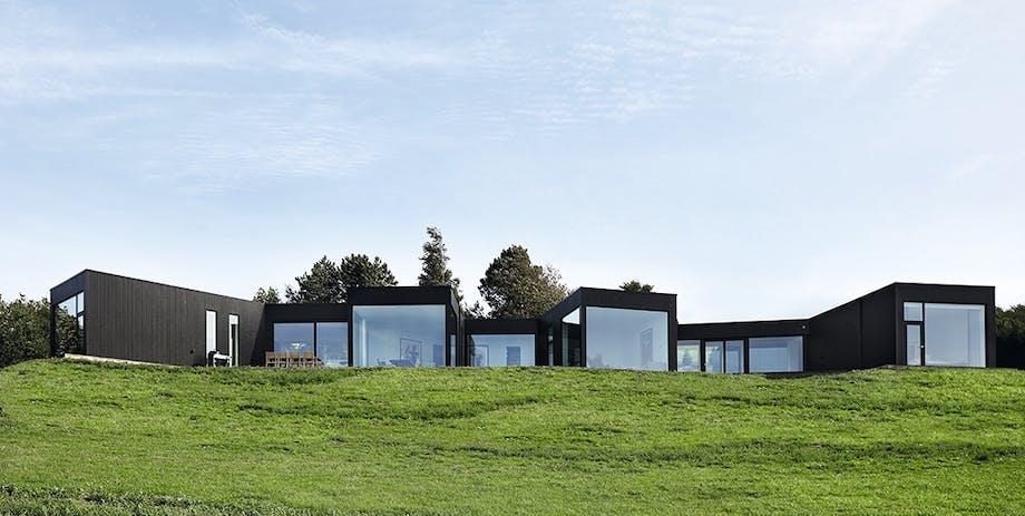 Hus med vinduer pegende ud mod græsskråning