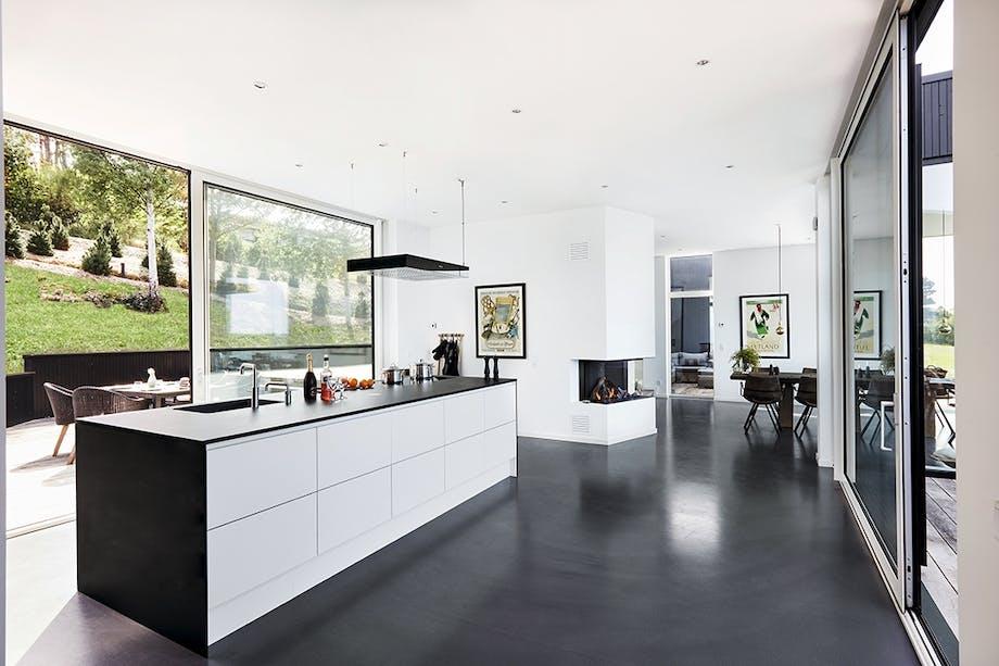 Køkken i sorte og hvide elementer med åben terrassedør