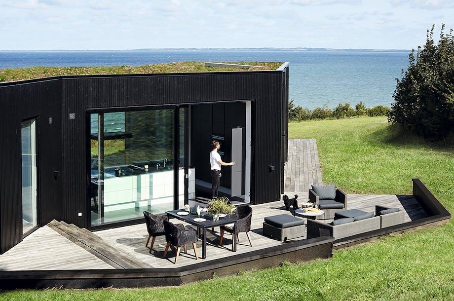 Hus i sort træ med stor træterrasse med havemøbler