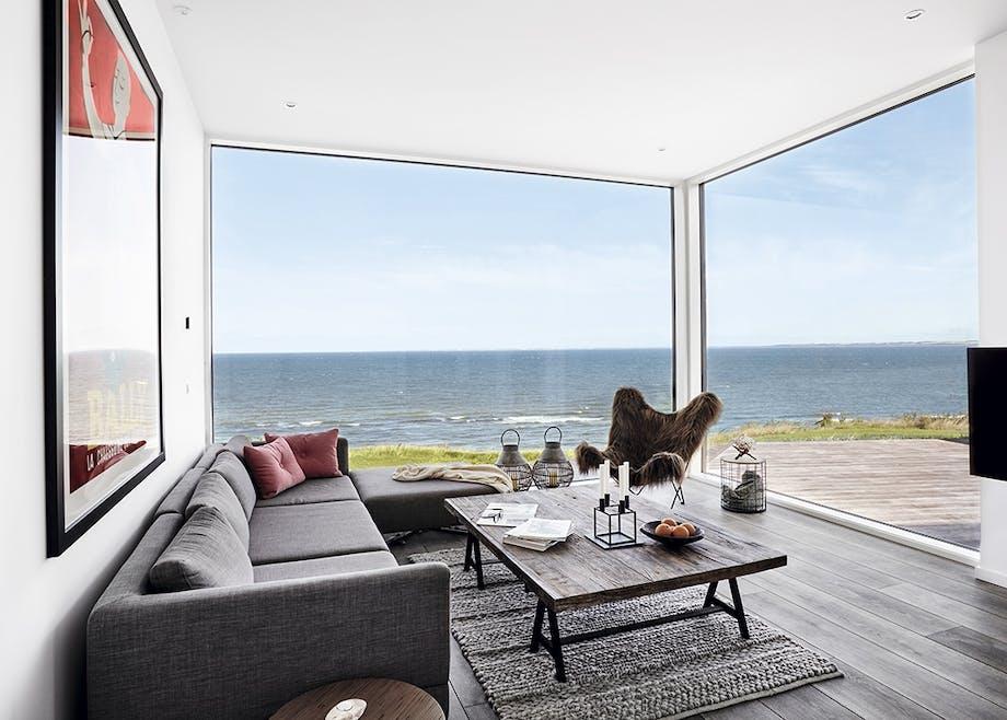 Opholdsstue med sofa og lænestol og udsigt udover havet