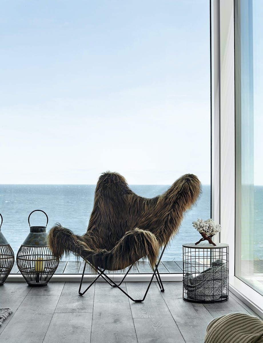 Lænestol med skindtæppe foran stort vindue med udsigt til havet